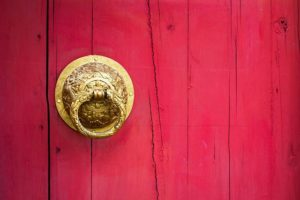 Pink wooden door with an ornate, golden door knocker on the right side of the frame.