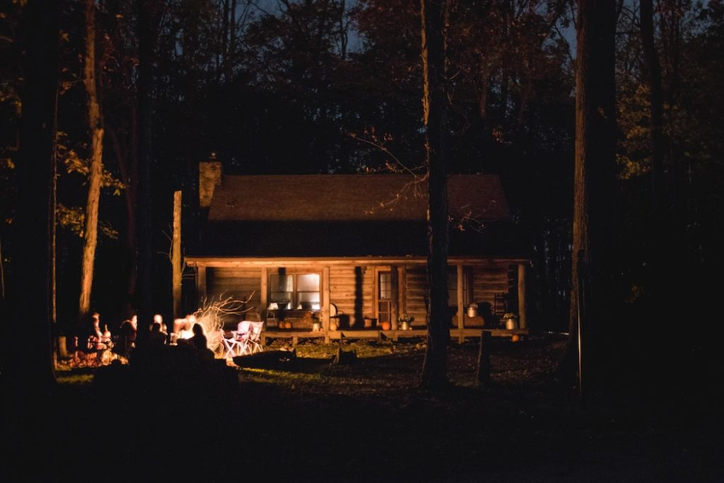 cabin at night lit by a campfire with people around it