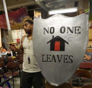 Antonio Ennis, community organizer at City Life / Vida Urbana, with sword and shield