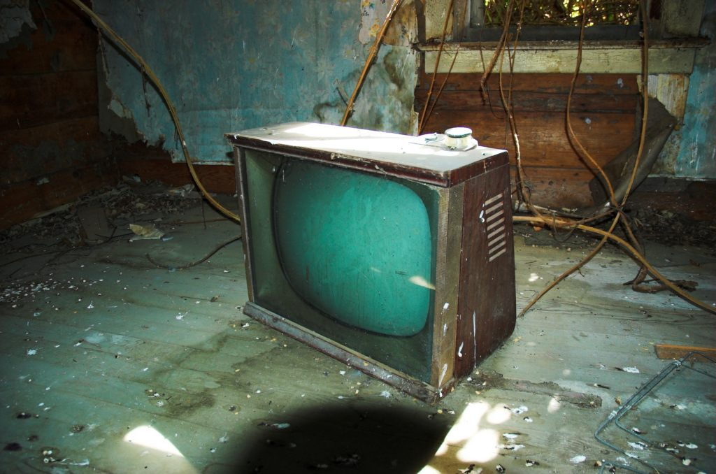 Old television set floating in damaged room