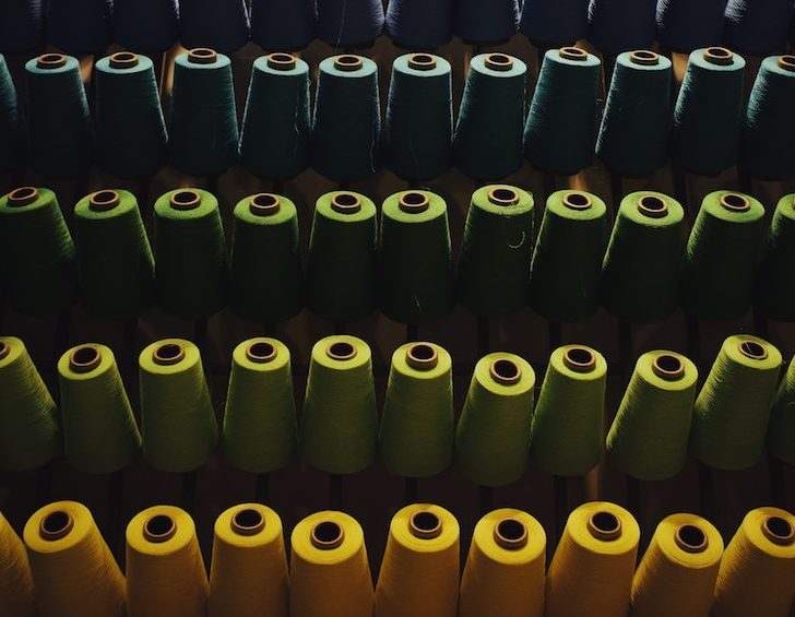 numerous spools of thread arranged in color order