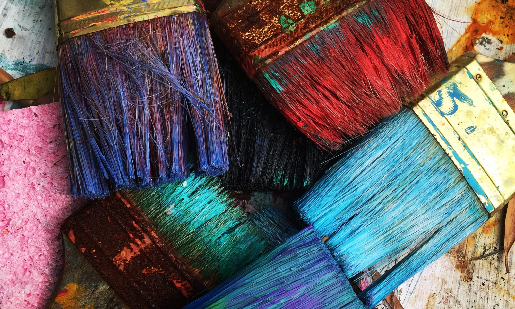 several paintbrushes dipped in different brightly colored paint