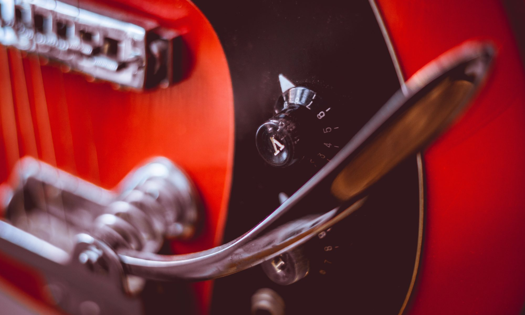 A close up of a red and black electric guitar.