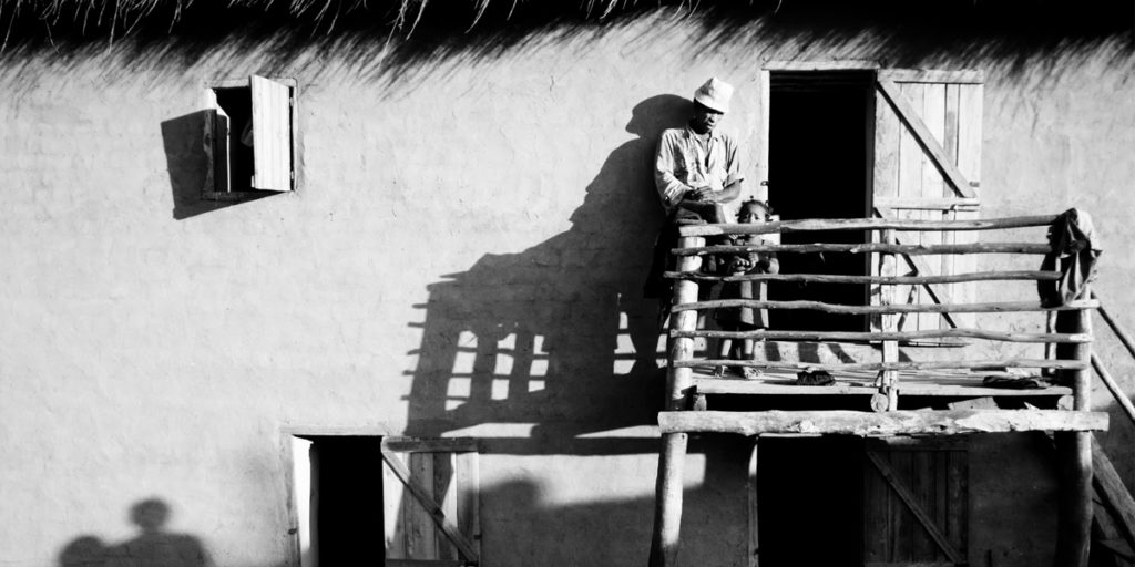 Black and white photo of man on balcony.