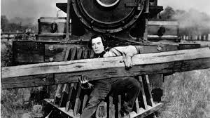Buster Keaton on the cowcatcher of a train engine, holding a large piece of lumber