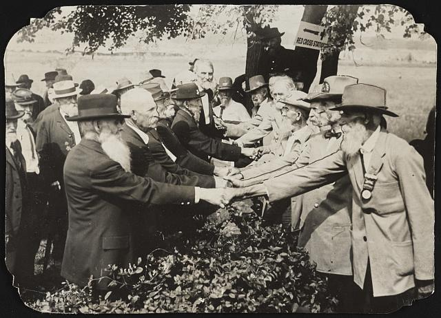 Union and Confederate veterans of the Civil War shake hands at a reunion to mark the 50th anniversary of the end of the war