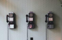 three rotary telephones on a wall