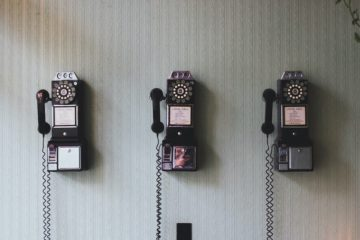 three rotary telephones on a wall