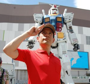 Daniel Fandino, a PhD Candidate in History at MSU, salutes the camera while standing in front of a towering Gundam, a giant robotic mech.