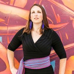 Elizabeth LaPensee, Assistant Professor of Media and Information at Michigan State University, stands in front of a painted mural, hand on hip, and looks stoically at the camera.