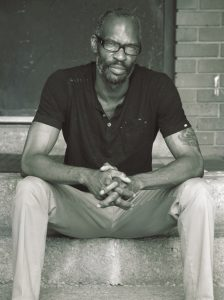 Cartoonist Ho Che Anderson sits on the cement steps of a building in a black short and khaki pants.