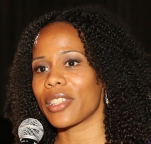 Sika Dagbovie-Mullins is confidently speaking into a microphone at an event