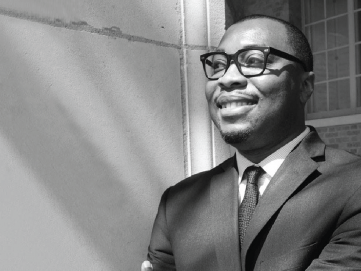 In this black and white photograph, Associate Professor Karlos K. Hill, a black man in a charcoal suit and tie, is smiling at something off-camera to his right.