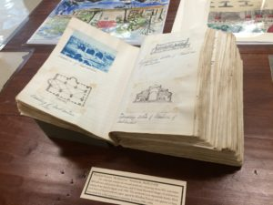 Open book with drawings in a display case